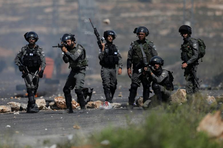 An Israeli border policeman aims his weapon at Palestinian protesters during clashes at a protest in support of Palestinian prisoners on hunger strike in Israeli jail, near Ramallah