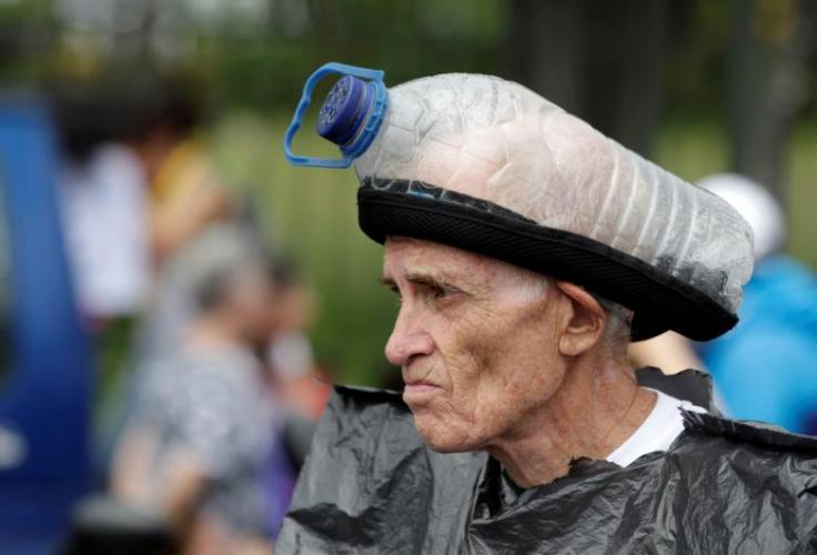 An opposition supporter looks on with a home-made gas mask on his head during a blockade in an avenue while rallying against Maduro in Caracas