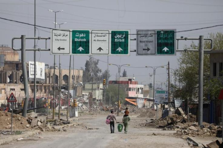 Civilians carrying their goods walk along a street in an area controlled by Iraqi forces in Mosul, Iraq