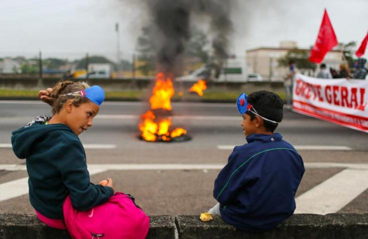 Children stand near a barricade on Dutra road during a protest against President Michel Temer's proposal reform of Brazil's social security system in the early hours of general strike in Sao Jose dos Campos